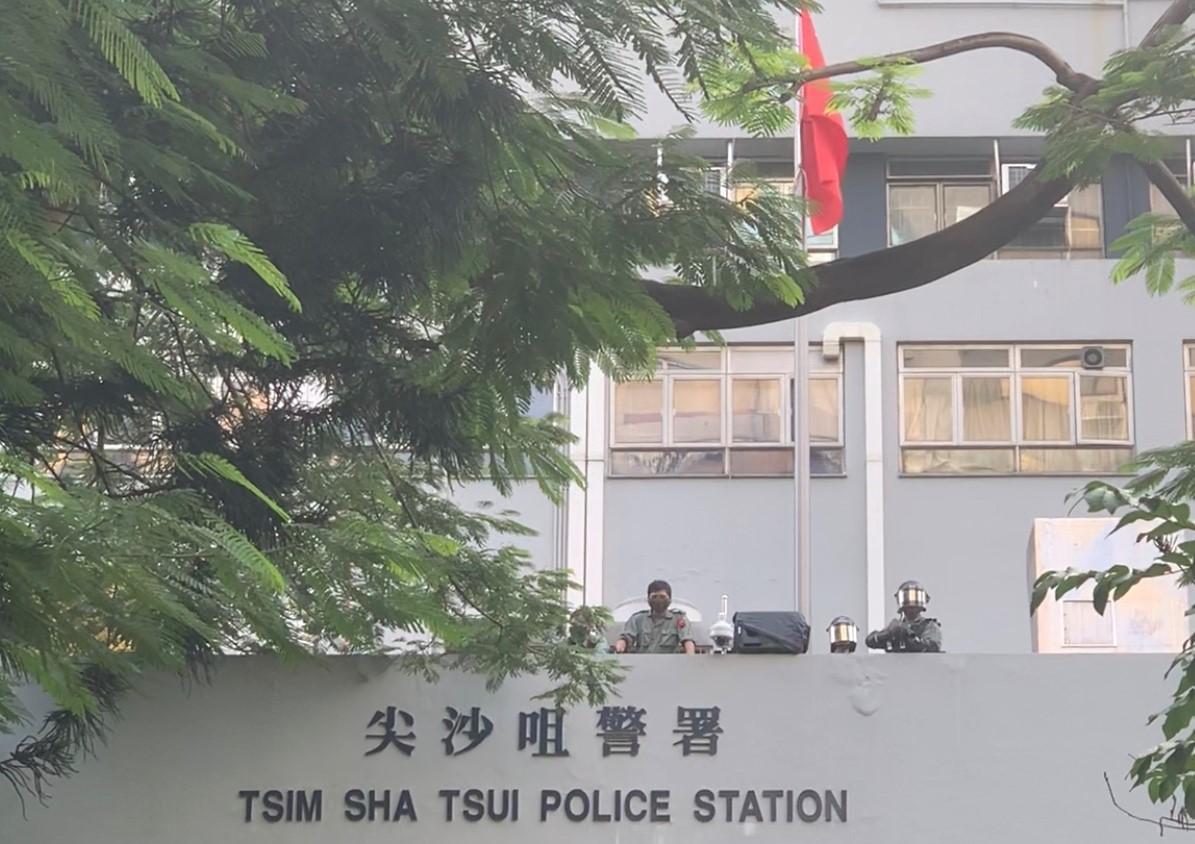 """香港""""反紧急法""""游行12日下午举行,示威民众行经尖沙咀警署前,警方如临大敌,持枪戒备。(记者郑崇生摄)"""