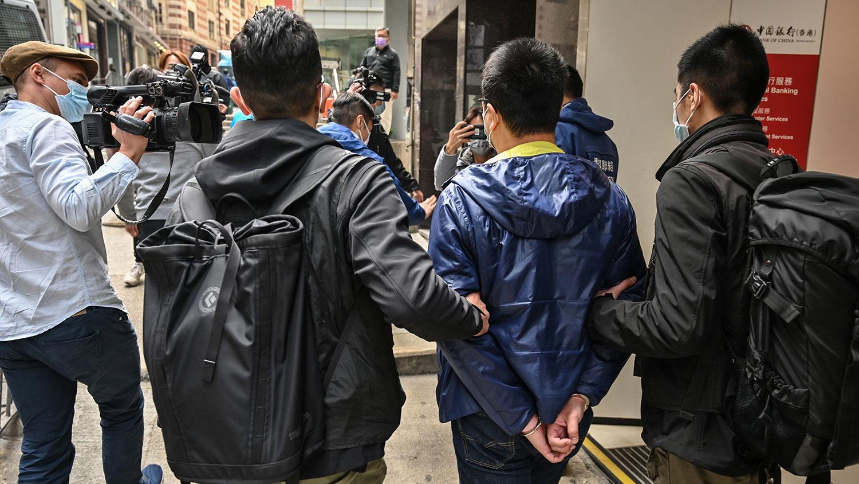 """2021年1月6日,香港警方出动千名警员进行大抓捕,53名民主派人士,被指去年参与初选,涉嫌""""颠覆国家政权""""。图为,现任香港西贡区议会主席兼欣英选区区议员钟锦麟Ben Chung(右二)被警察带走。(法新社图片)"""