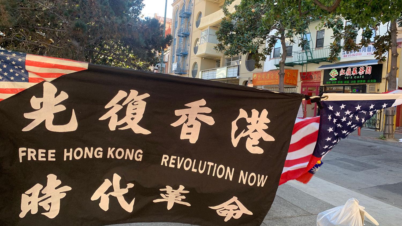 """花园角广场上,张女士悬挂的""""光复香港,时代革命""""旗、美国国旗及青天白日满地红旗随风飘动。(孙诚提供)"""