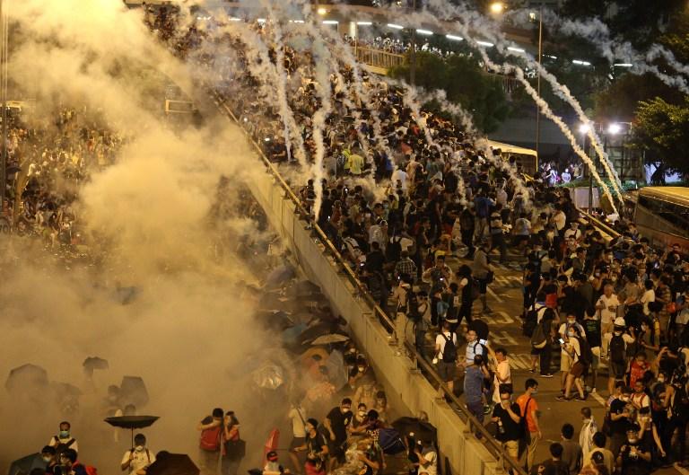 图片:香港警方向抗议人群发射催泪弹。(法新社)