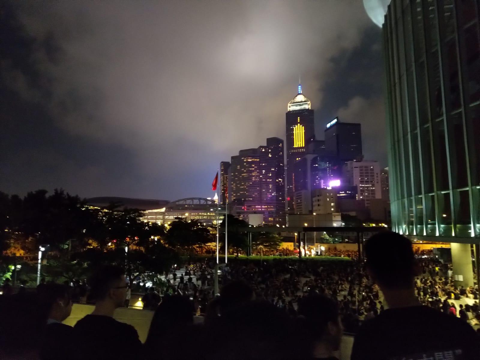 """2019年6月16日,近200万不满香港政府拒绝撤回""""送中""""条例的香港市民举行了示威游行。图为留守政府总部大楼外的香港市民。16日深夜 。(戴维提供)"""