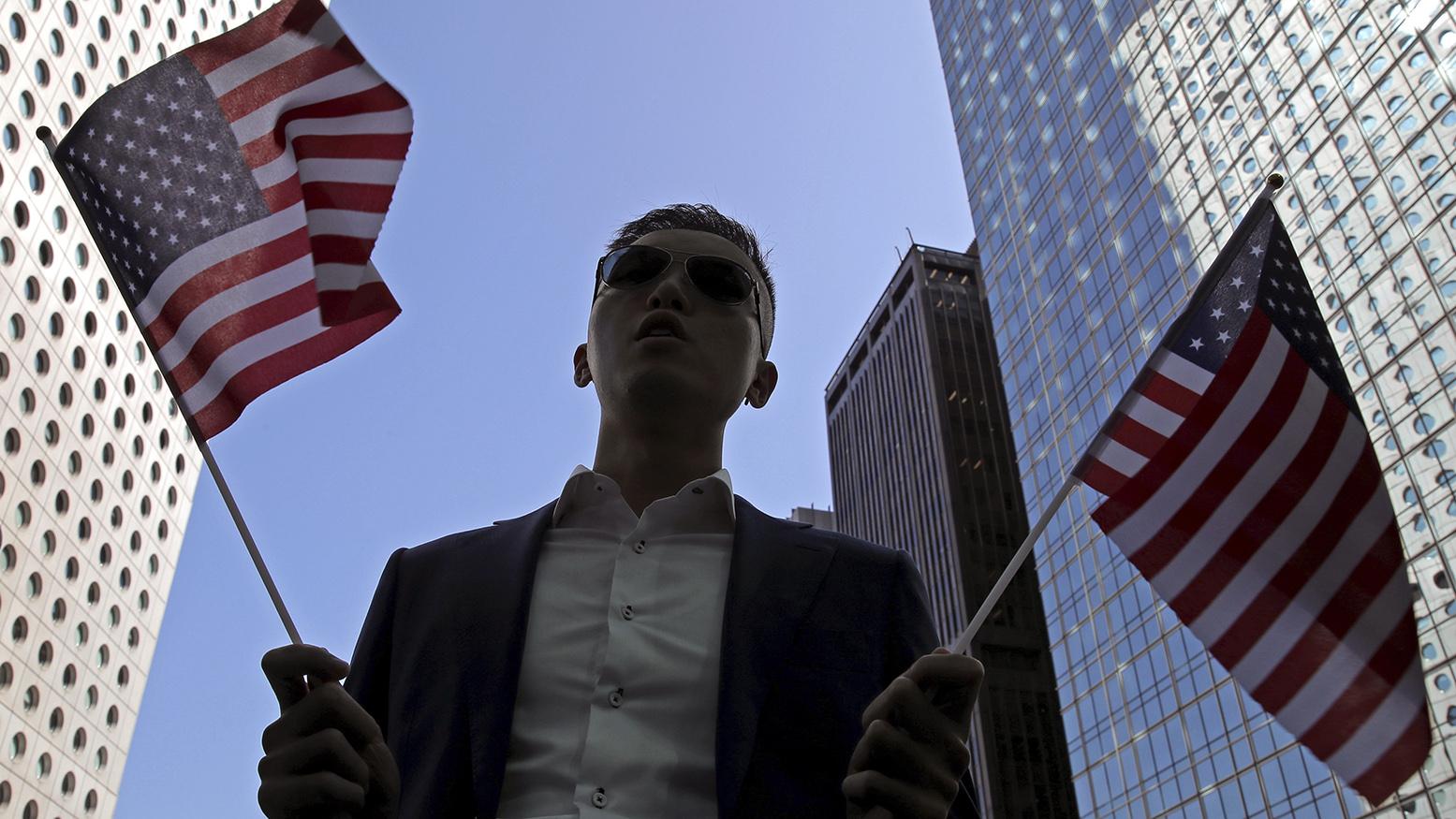 2019年11月28日,一名香港抗议者举着美国国旗。(美联社)