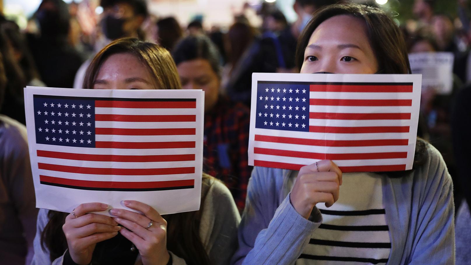 2019年11月28日,两名香港抗议者举着美国国旗在街头抗议。(美联社)