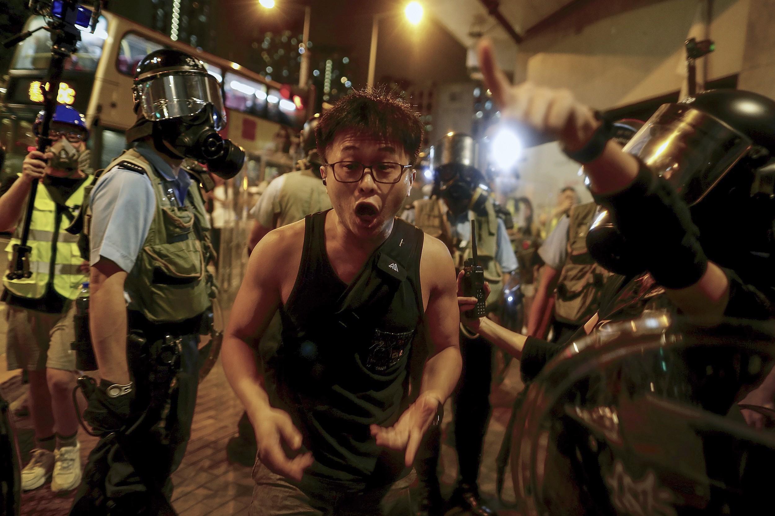 一名香港抗议者在警察要求他离开时与警察争执。(美联社)