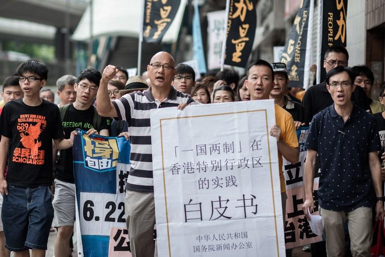 图片:2014年6月11日,香港的示威者们在中联办前集会,抗议中国国务院早前发布的《一国两制在香港特别行政区的实践》白皮书。(法新社)