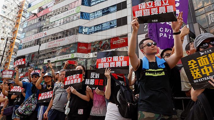 """2019年7月21日,香港反送中大游行时,示威者举着标语""""成立独立调查委员会""""。(美联社)"""