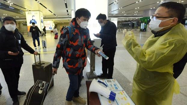2020年2月17日,浙江省杭州市一名旅客向火车站检疫人员出示手机中的绿色健康码以证明健康状况。 (路透社)
