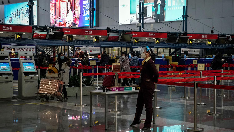 2021 年 2 月 3 日,北京首都国际机场出发大厅,乘客在值机柜台办理乘机手续。 (美联社)