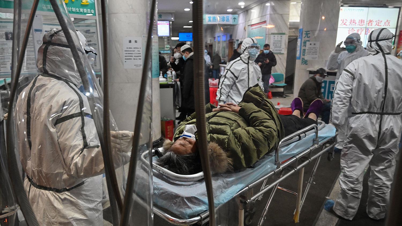 中国新型冠状病毒肺炎疫没有受控迹象,也使医疗体系面对前所未有的危机。图为2020年1月25日,身穿防护服的医务人员正运送病人到达武汉市红十字会医院。(法新社)