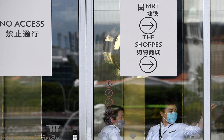 人口以华人占多数的新加坡被视为武汉肺炎疫情重灾区,至今有超过80人确诊感染,人数是全球第三。图为,2020年2月18日,工作人员在新加坡滨海湾购物中心指示告示牌旁边。(法新社)