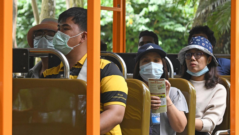 新加坡和中国关系密切。去年到访新加坡的外籍旅客以中国游客占比例最高。图为,2020年2月18日,在担心COVID-19新型冠状病毒扩散的情况下,游客戴着防护口罩,在新加坡动物园的电车中游览。(法新社)