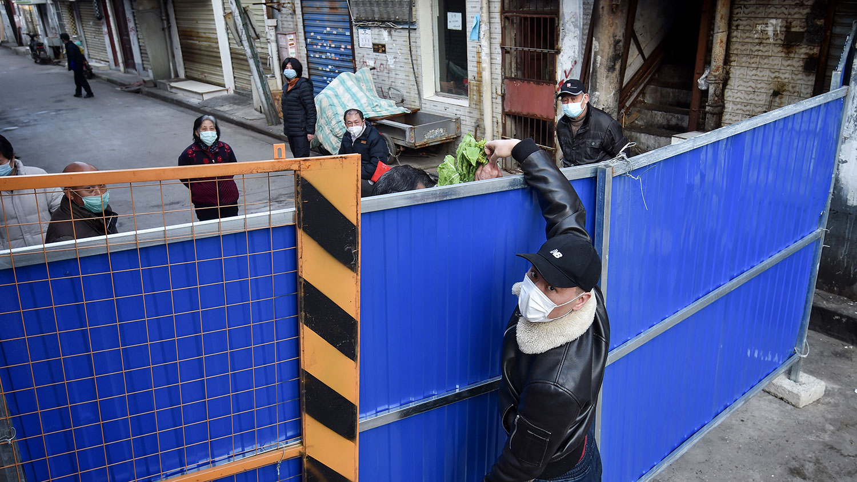 2020年2月23日,在湖北省武汉市,一名男子正在向障碍物另一侧的人运送蔬菜,以阻止其他人进入。(法新社)