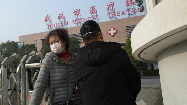 两名市民离开湖北省武汉市医疗救治中心。一名肺炎患者2020年1月12日在该中心死亡。(法新社)