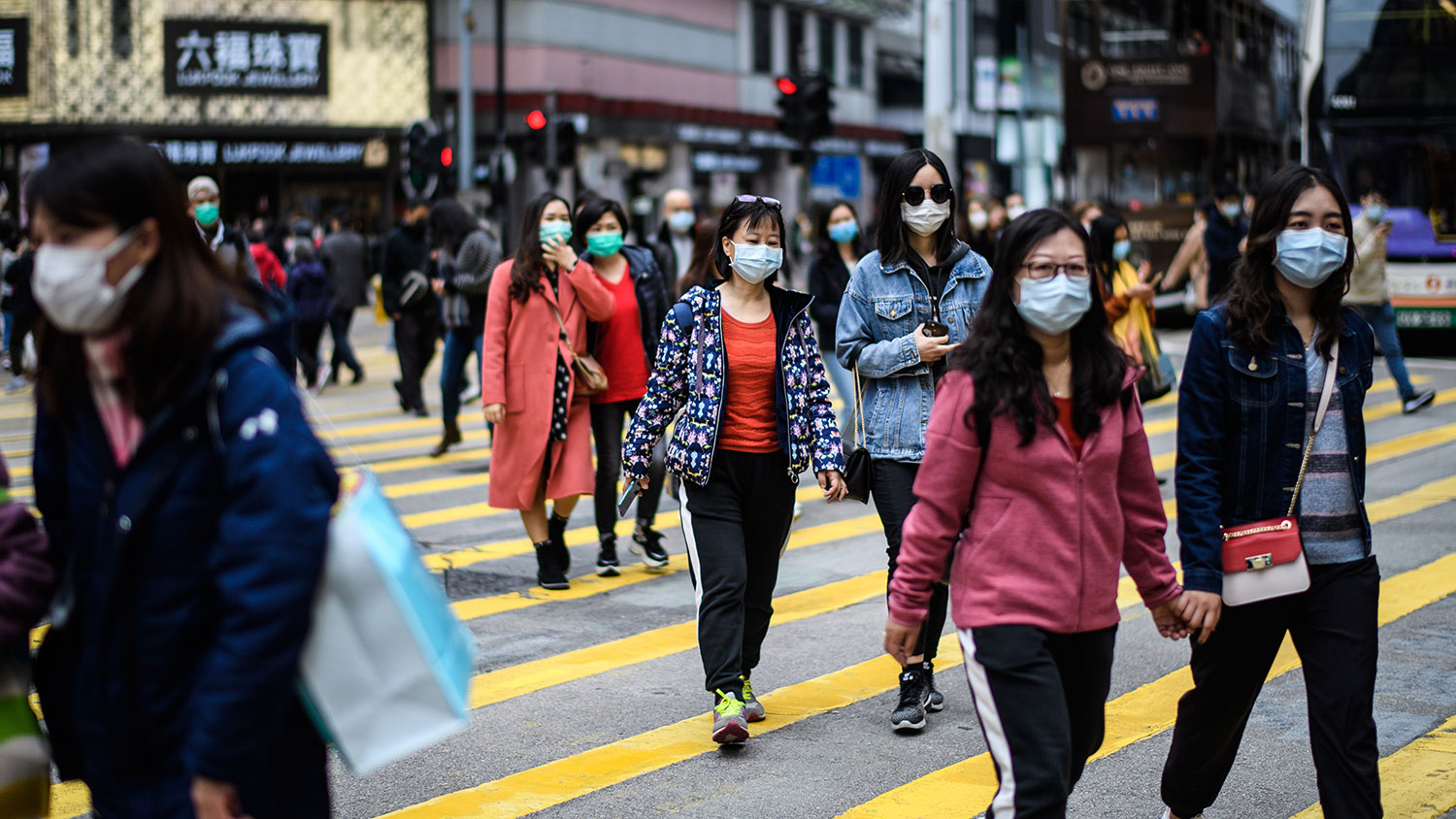 Pedestrians wearing masks cross the road during the Lunar New Year holiday in Hong Kong, Jan. 27, 2020. (AFP)