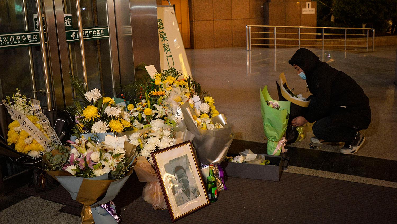 2020年2月7日,湖北武汉市中心医院后湖分院外,一名武汉市民在已故眼科医生李文亮的照片旁边摆放鲜花。(法新社)