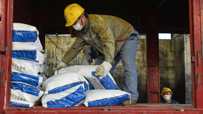 學者擔心徵用措施會被濫用。圖爲2020年1月30日,一名工人在湖北省孝感市的一家工廠運送消毒劑袋。(法新社)