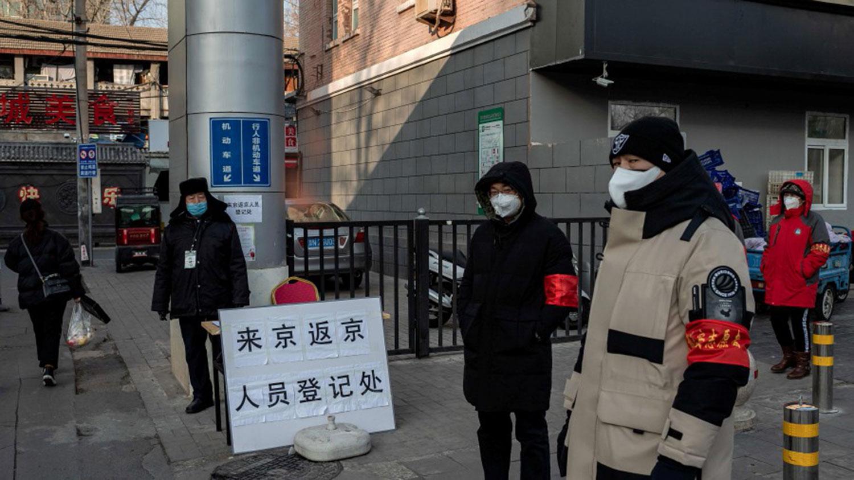戴防护口罩的保安人员和志愿者站在居民进入北京之前,会对其进行身份识别和温度检查。 (法新社)