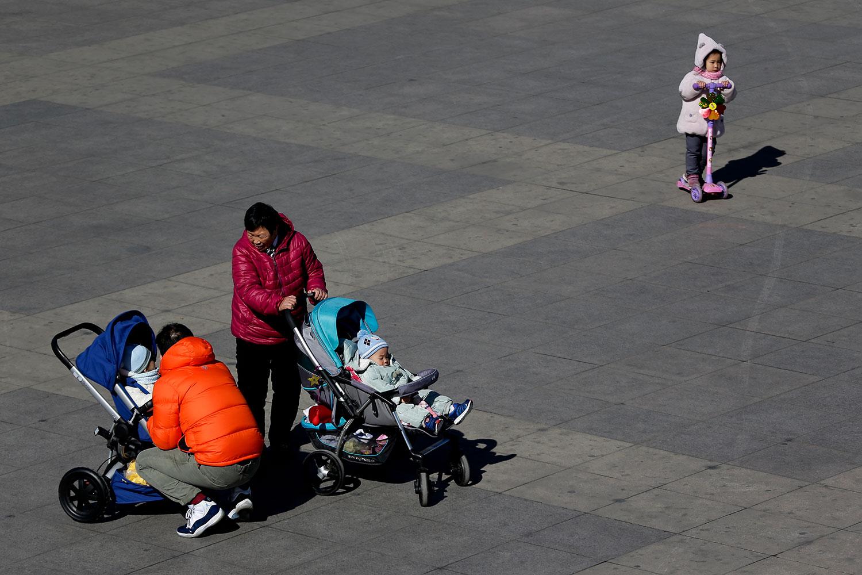 北京市民將嬰兒帶到公園裏。(美聯社)