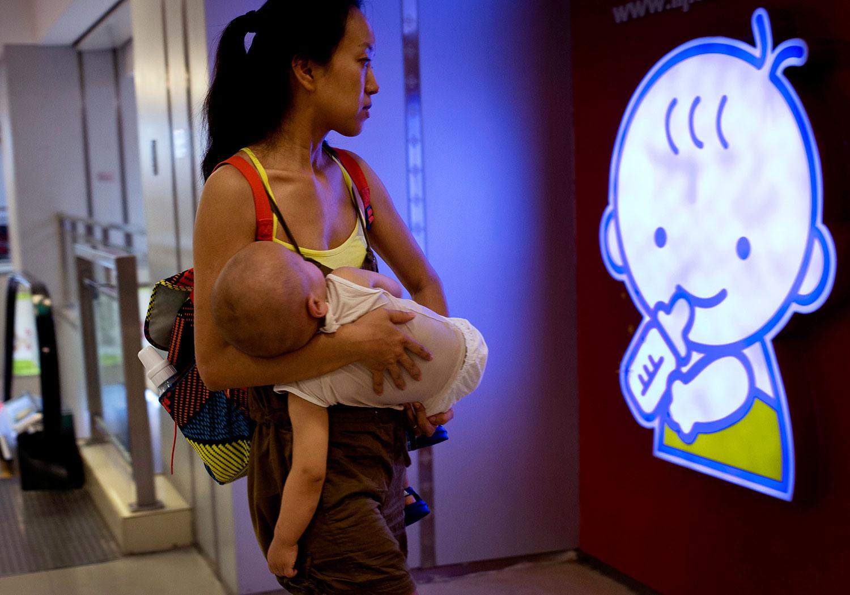 圖爲,一名攜帶嬰兒的婦女,在北京購物中心的嬰兒卡通標誌前。 (美聯社)
