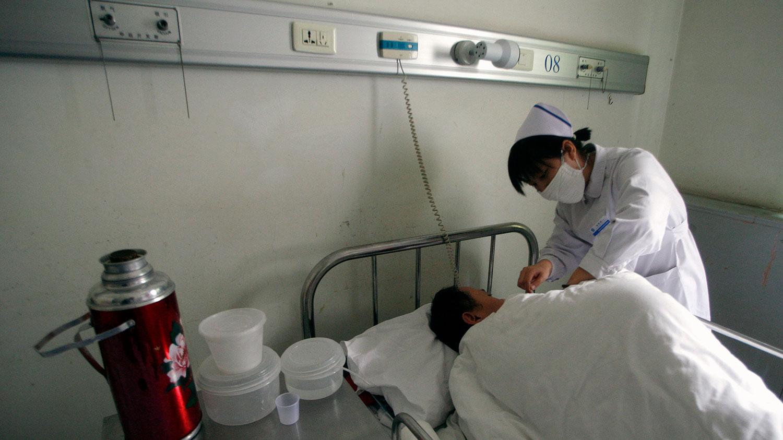 根据官方数据,到2018年年底,中国估计有125万人感染艾滋病毒。图为一名护士在北京佑安医院艾滋病病房检查病人的体温。(路透社)