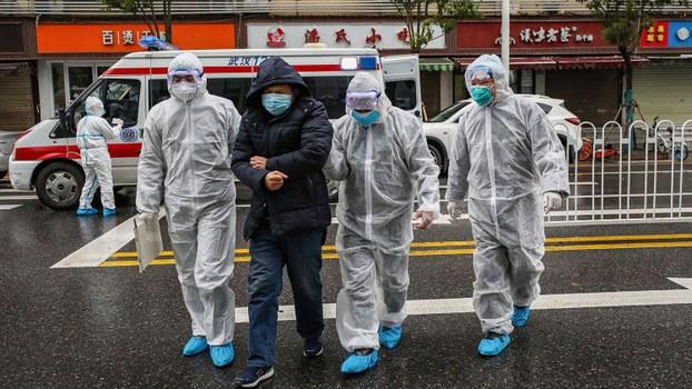 湖北省潜江市政府推出奖励潜在患者自查新冠肺炎措施引发热议。图为武汉市一新冠肺炎患者在医务人员搀扶下走进医院。(法新社)