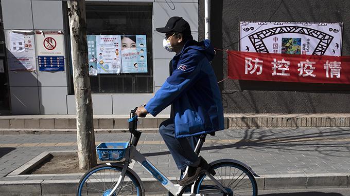 """2020年3月12日,北京一名男子骑车经过""""防控疫情""""宣传口号。(美联社)"""