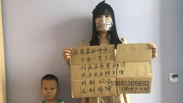 问题疫苗受害儿童的家长何方美举牌抗议(志愿者提供/记者乔龙)