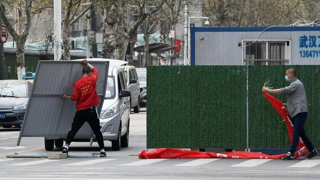 2020年3月21日,工人消除了武汉街道上的障碍。(路透社)