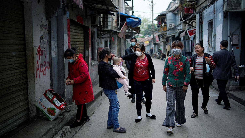 图为,2020年4月5日,武汉市居民在一个被障碍隔离的老居民区。(路透社)