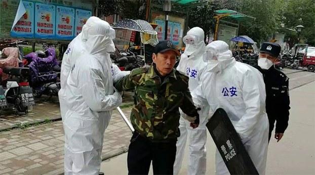 武汉颐和家园小区内,一住户未戴口罩,被公安控制。(志愿者提供/记者乔龙)
