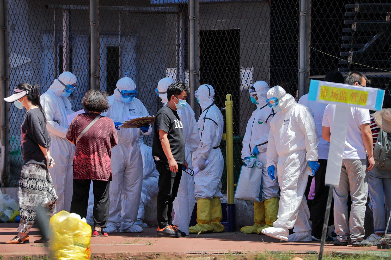 2020年6月14日,身穿防护服的工作人员核对市场人员进行核酸检测人的名字。(美联社)