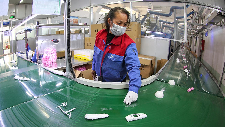 图为,2020年2月10日,山东省一家工厂生产温度计的工人回到岗位工作。(法新社)