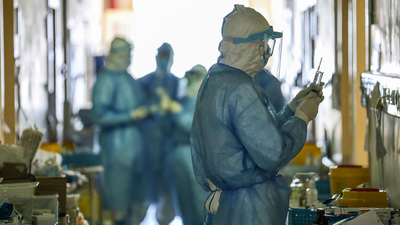 有人一套防护服穿两天,也有人自制防护用品,武汉医护人员成了最容易感染的群体。图为2020年2月16日,湖北省武汉市红十字会医院的医务人员在隔离病房工作。(法新社)