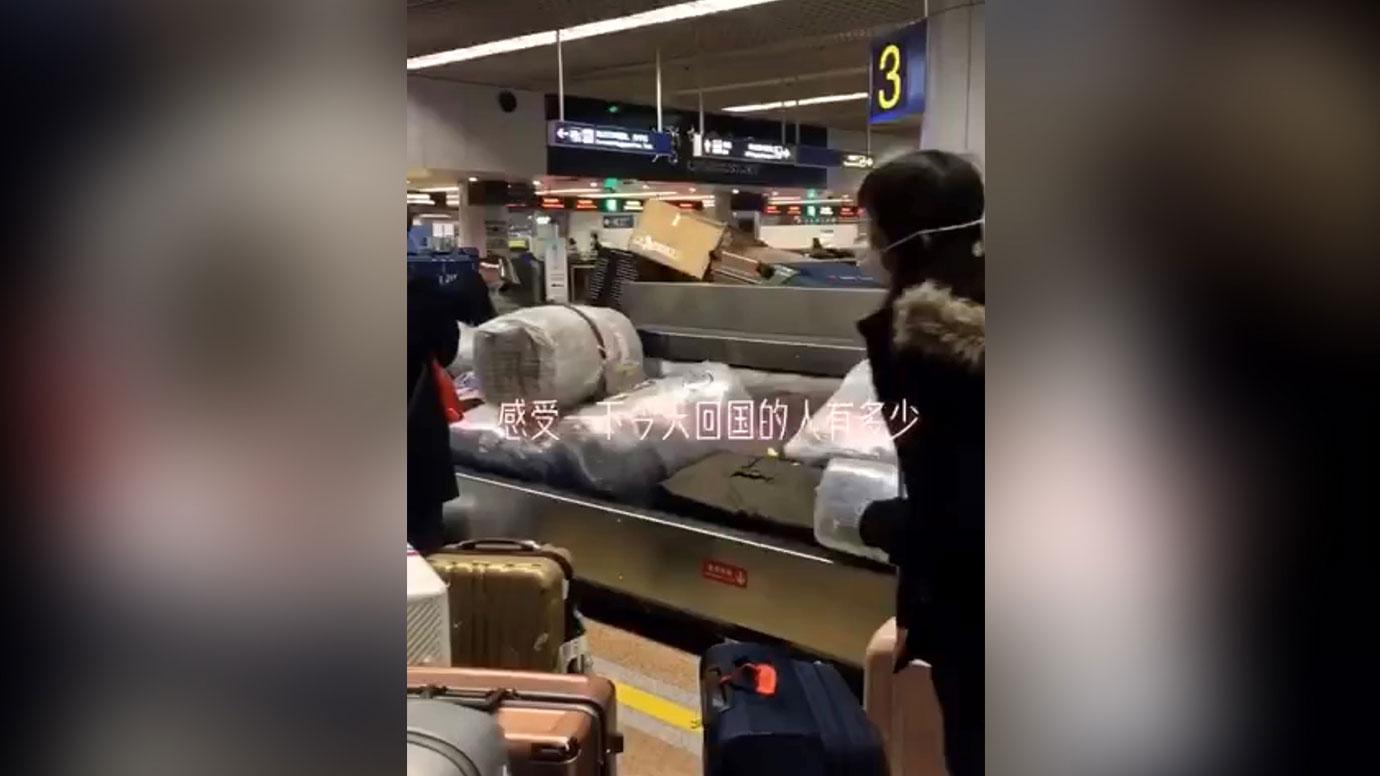 北京国际机场行李传送带上,众多海外华人抵达。(视频截图)