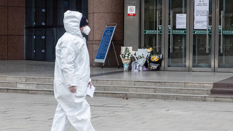 图为,2020年2月7日,一名医务人员在武汉中心医院已故的眼科医生李文亮的鲜花旁走过。(法新社)