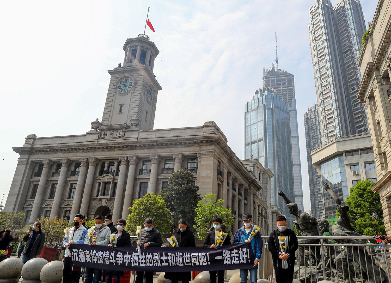 图为,2020年4月4日,人们在湖北省武汉市汉口海关降半旗的汉口海关大楼外面默哀片刻。(路透社)