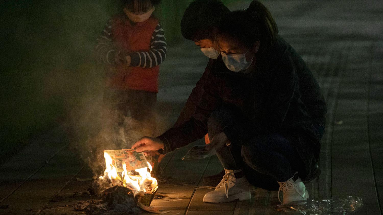 图为,2020年4月4日,湖北省武汉市一家人在街上为其亲人烧纸祭。(美联社)