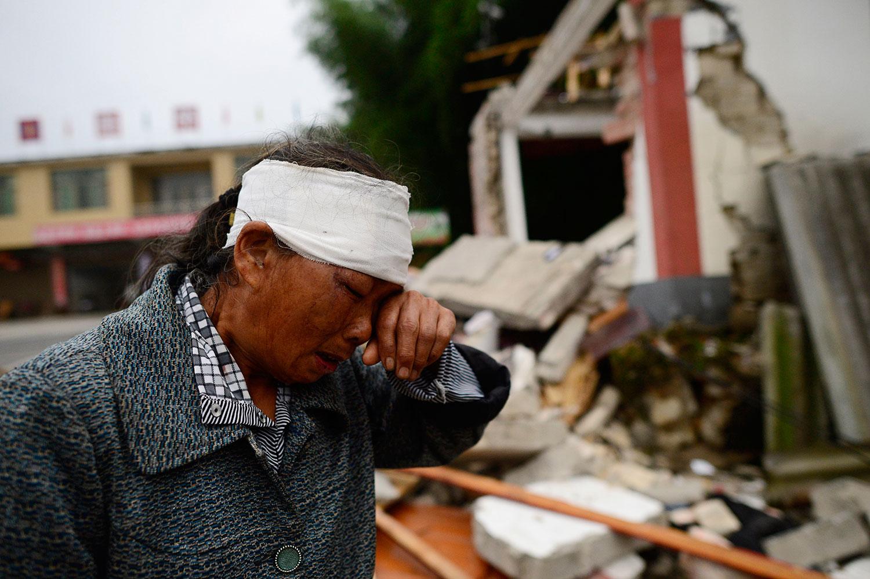 2019年6月17日,四川宜宾长宁县深夜发生6级地震,造成房屋倒塌,逾两百人伤亡。图为18日地震后,一名受伤的妇女在受地震破坏的建筑物附近。(法新社)