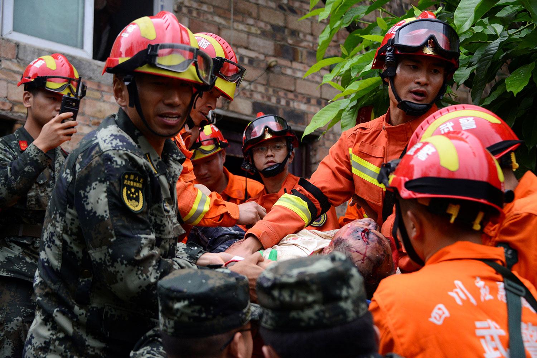 2019年6月17日,四川宜宾长宁县深夜发生6级地震,造成房屋倒塌,逾两百人伤亡。图为18日地震后,救援人员在担架上载着一名受伤的男子。(路透社)