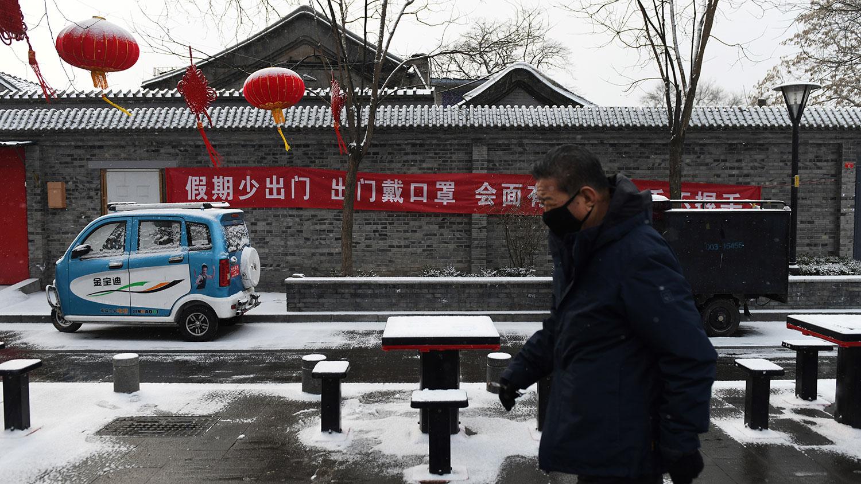 疫情之下,第一个彻底归零的行业挂红灯笼贴春联的余丰里民宿,目前已经大门紧闭。图为2020年2月5日,北京一条小巷挂着横幅标语:假期少出门,出门戴口罩....。(法新社)