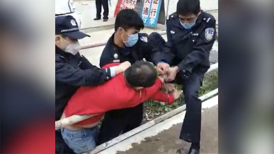 一男子拒未戴口罩被三名公安控制。(视频截图/乔龙提供)