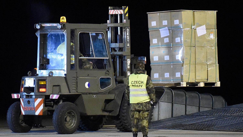图为,2020年3月22日,捷克士兵在帕尔杜比采巴尔杜比采机场卸下了一架从中国运送100吨以上医疗和防护装备的飞机,以阻止冠状病毒(COVID-19)的传播。(法新社)
