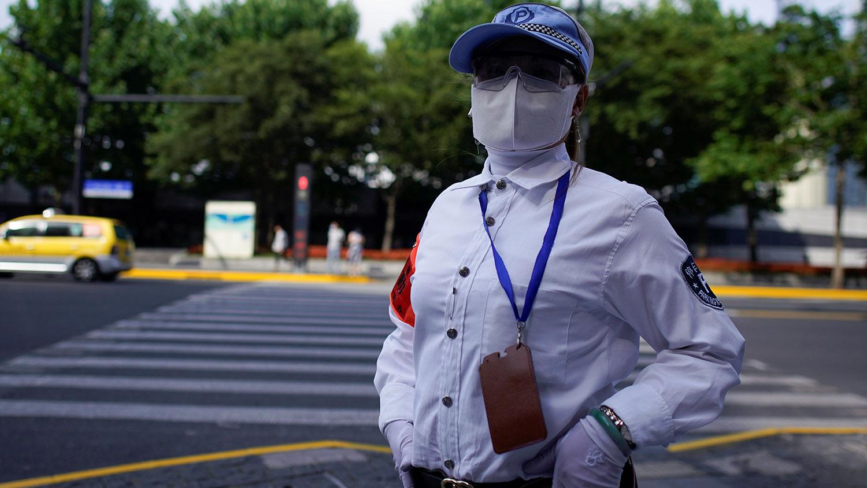 图为,中国冠状病毒病(COVID-19)爆发后,一名戴着口罩的停车管理人员站在上海的一条街道上。(路透社)