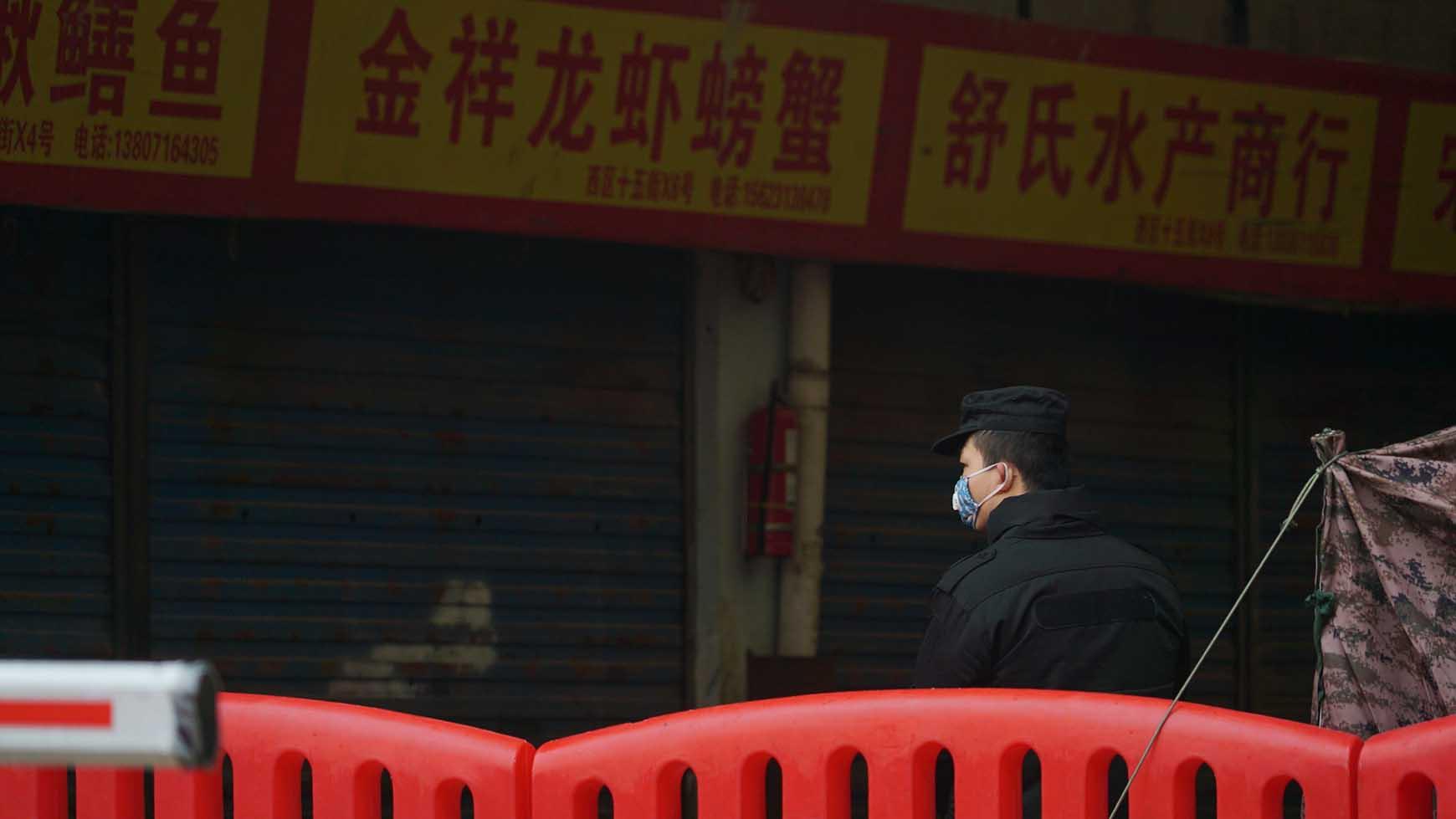 警察在多個民衆查出感染武漢肺炎的一個武漢農貿市場外執勤。(美聯社)