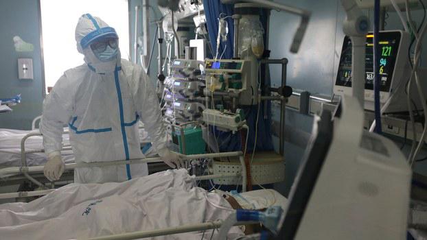 2020年2月13日,医务人员在武汉金银潭医院重症监护病房(ICU)内检查重症肺炎患者。(路透社)