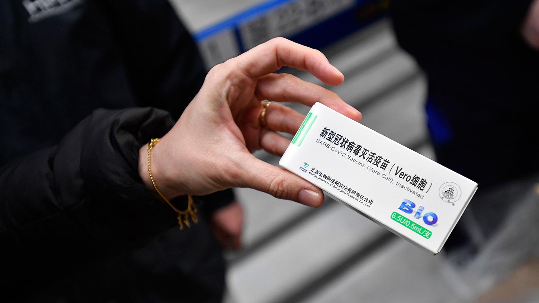 一名妇女手拿中国国药集团新冠疫苗药盒。 (美联社)