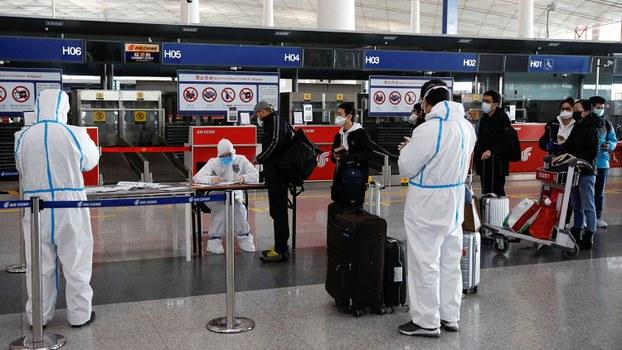 身穿防护服的工作人员正在北京首都国际机场对乘客进行登记(路透社)