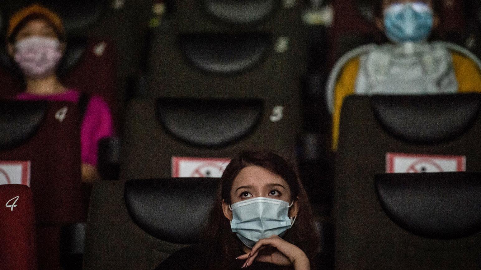 2020年7月20日,民众戴着口罩在武汉的一家电影院看电影。(法新社)
