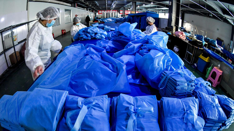 2020年1月27日,新疆维吾尔自治区乌鲁木齐市的一家医疗设备制造商的工厂里,工人在生产防护服和口罩的生产线上。(路透社)