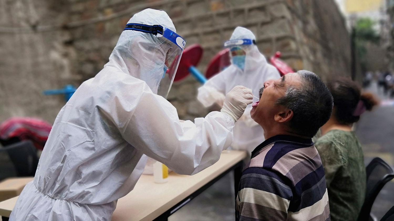 2020年7月19日,在新疆乌鲁木齐,医务工作者对居民进行新型冠状病毒检测。